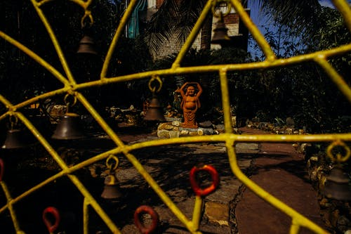 Yellow fence from iron in front of yard with Buddha statue and stones