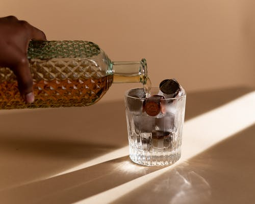 A Person Pouring Liquor in the Clear Glass with Coins