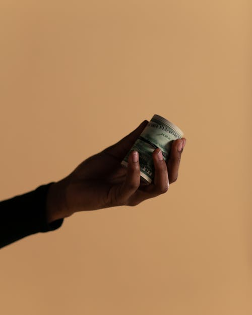 Person Holding Rolled Banknotes
