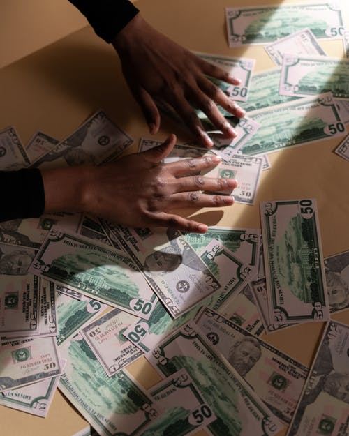 Person Holding Fan of Banknotes