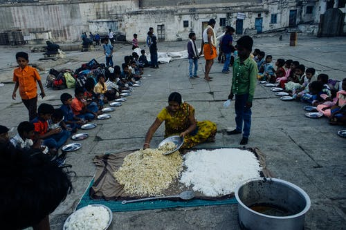 From above of old Indian woman serving food on plates while sitting on ground surrounded with kids in poor area