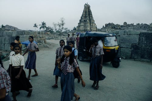 Group of serious Indian schoolgirls in similar shirts and skirts with ties walking against rickshaw in town