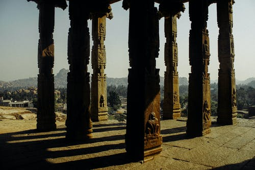 From above of aged stone pillars with carved relief of old Buddhist temple