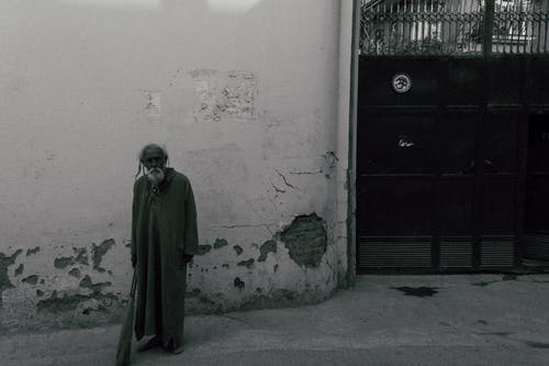 Black and white of full body senior bearded male in traditional wear standing near shabby wall of building and metal gate and looking at camera
