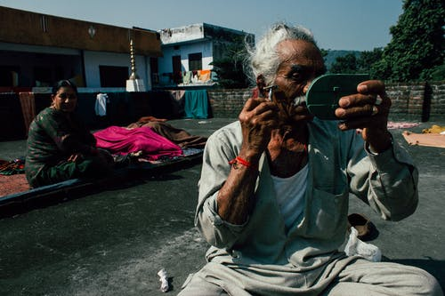 Aged Indian man in casual clothes sitting on ground on street with small mirror and shaving