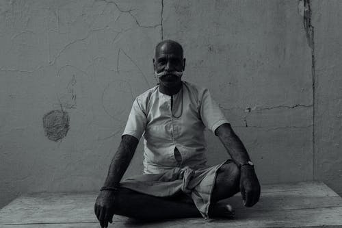 Focused ethnic man doing yoga on street