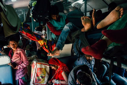 Poor people with many backpacks and bags in old crowded bus having trip during holiday