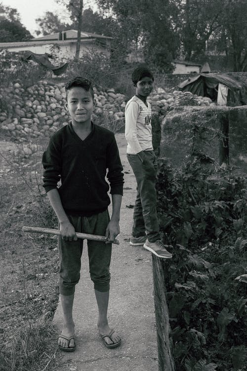 Black and white of young Indian boys looking at camera while standing in yard with plants and working