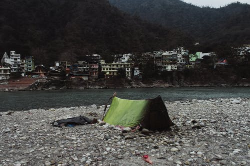 Green tent of poor person located on stony shore of calm river on cloudy day