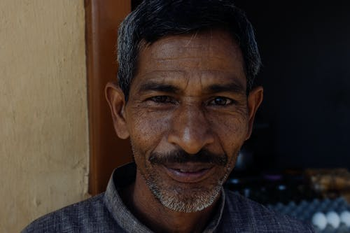 Smiling Indian man in casual clothes looking at camera while standing near entrance of house