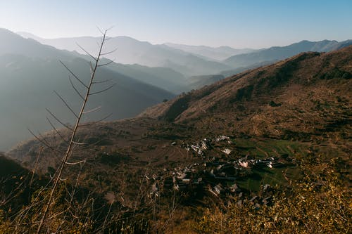 Spectacular view of empty land with small settlement surrounded by hills on day with good weather