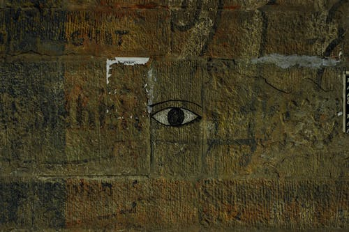 Eye picture painted on center shabby damaged concrete wall with scratches and stains