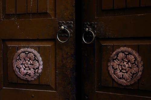 Old wooden door with ornamental elements and iron door handles