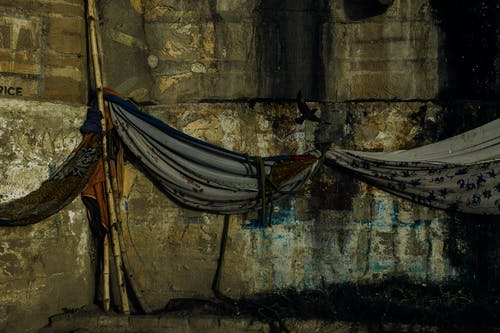 Fabric hammocks hanging on bamboo stick against aged damaged weathered wall of embankment