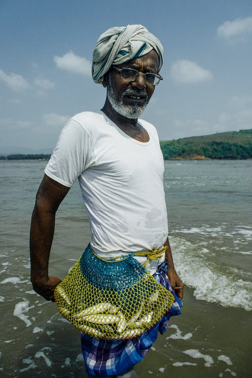 Indian male in eyeglasses standing in river with fish in net sack on waist while caching seafood