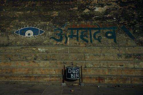Shabby stone wall with eye ornament and Hindi inscription