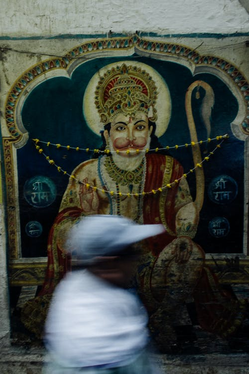 Side view of ethnic man moving past Hinduism image painted on wall in India