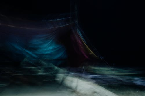 Dynamic abstract obscure background of draped bright cloth in motion hanging in darkness