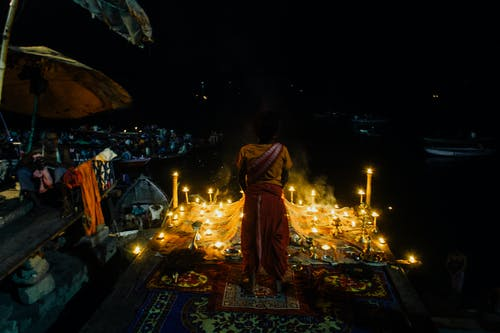 Indian woman praying with burning candles at night