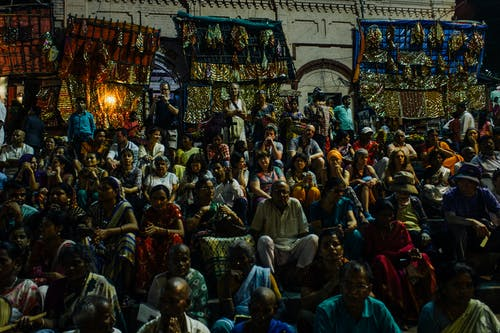 Crowd of ethnic people sitting on rows on event