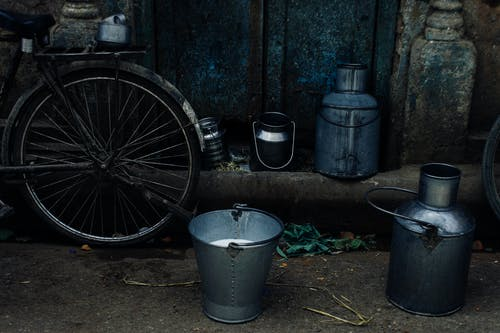Tin vessels and metal bucket with milk placed near bike leaned on shabby rusty wall