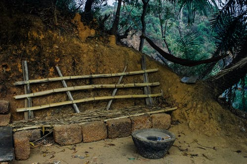 Stone fireplace for cooking near seats for tribal inhabitants made of bamboo and granite in jungle