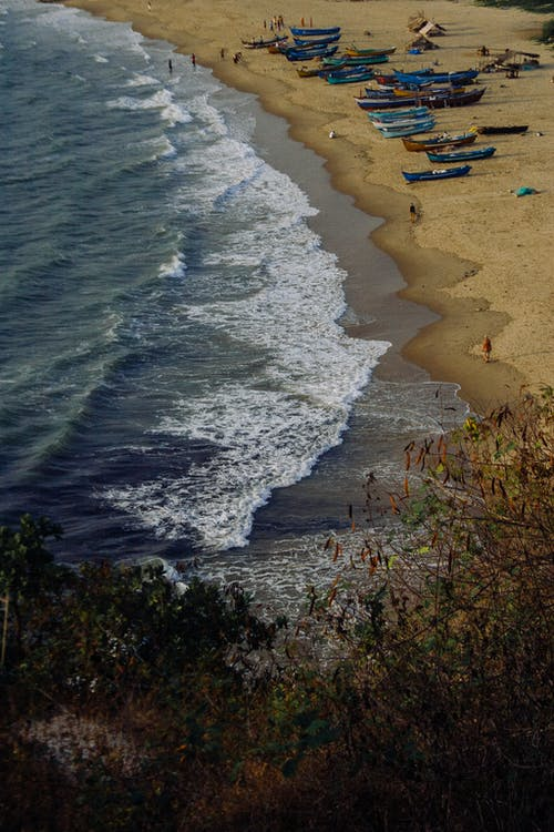 Sandy beach with boats washed by foamy sea