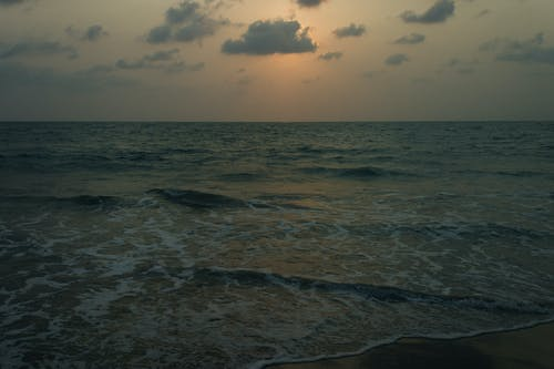 Picturesque seascape of endless sea with waves running on wet sandy shore under sundown sky