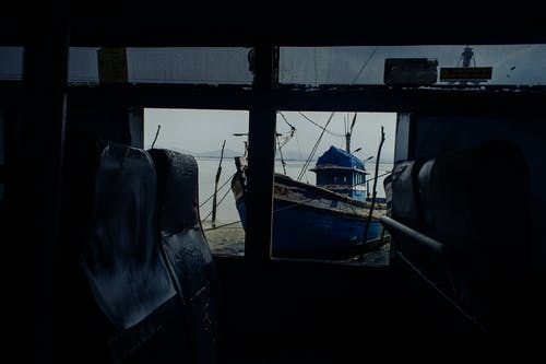 View through window of worn out bus with broken windows on sandy coast with wooden boat