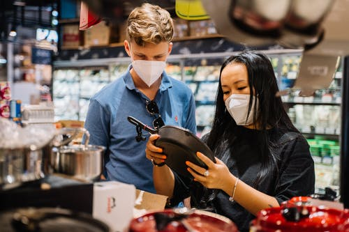 Couple Wearing Face Masks Looking At Kitchenware Inside A Supernarket