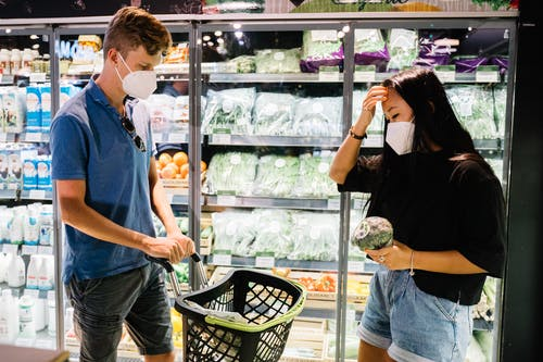 Couple Wearing Face Masks Shopping Inside A Grocery