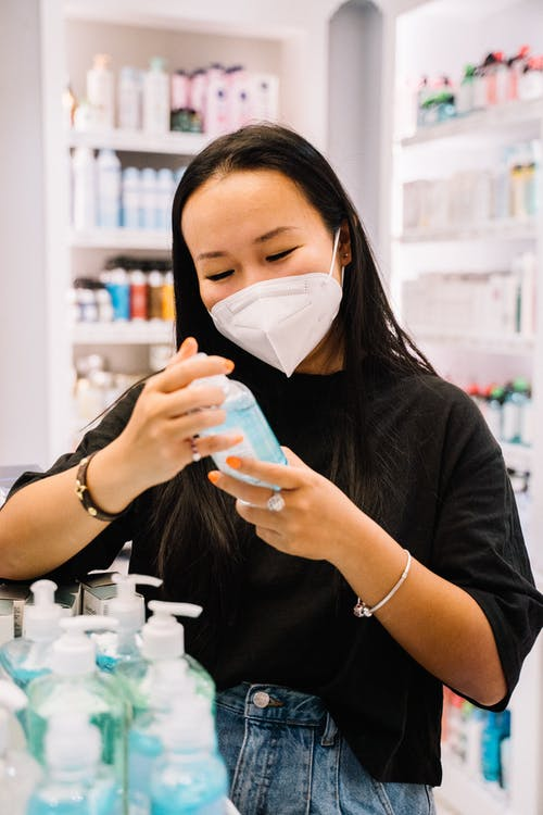 Woman With Face Mask Holding A Bottle Of Hand Sanitizer