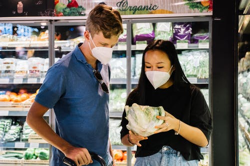 Couple With Face Masks Shopping For Fresh Vegetable