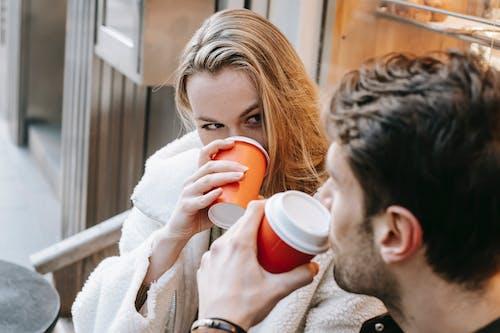 Woman in White Sweater Holding Orange Ceramic Mug