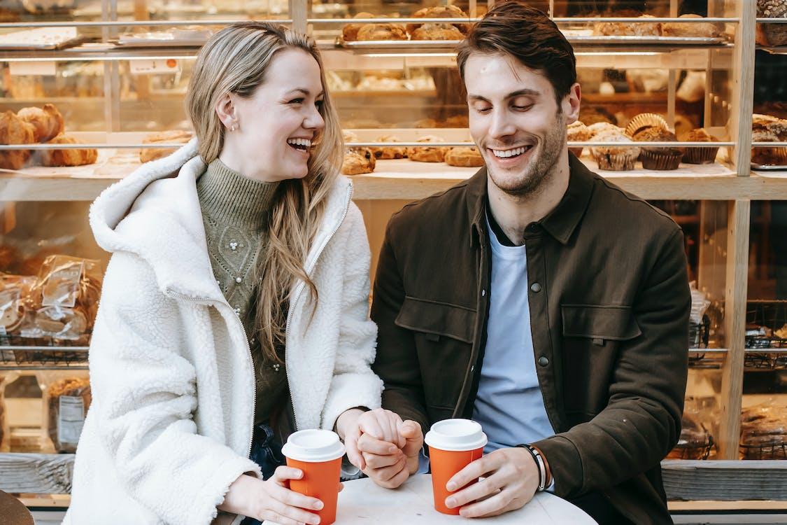 Мужчина и женщина улыбаются, держа кофейные чашки
