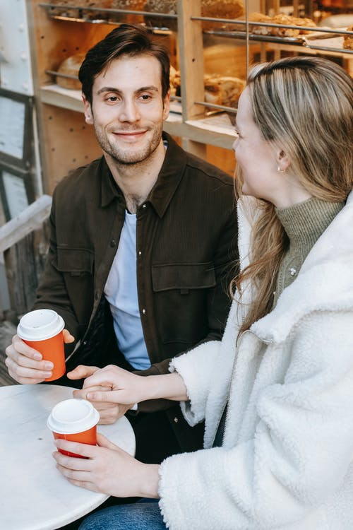 High angle of young positive boyfriend holding hands with girlfriend during date in outdoors cafeteria with hot drinks in daylight