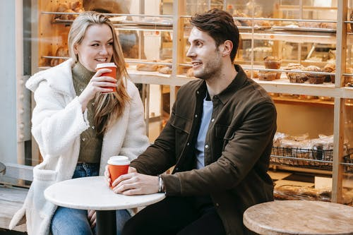 Delighted young couple having date in street cafeteria