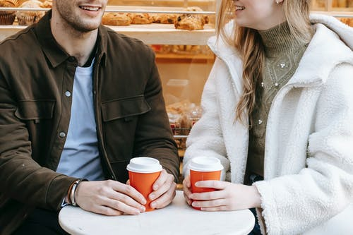 Unrecognizable happy couple in casual wear sitting at small table and having hot beverage in paper cup in cafe