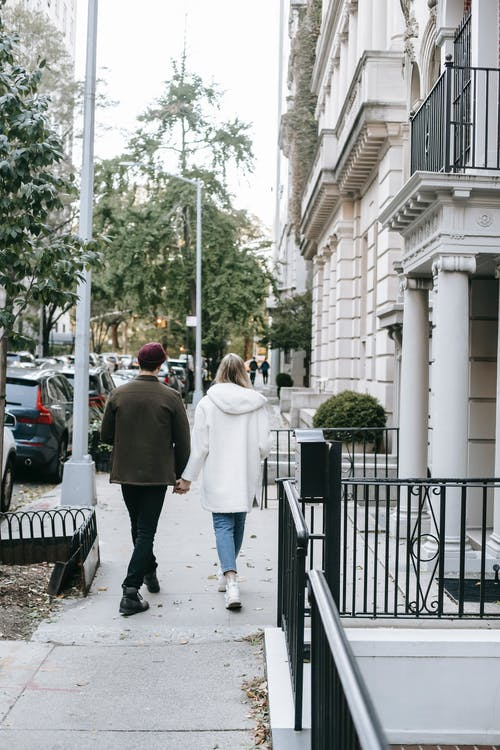 Man and woman walking along old building in city