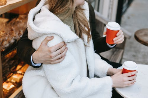 Young man and woman cuddling in bakery while drinking hot beverage