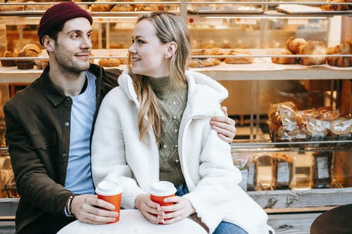 Cheerful young man and woman embracing sitting at small table in cafeteria and having hot drink