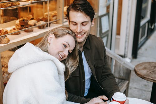 Happy woman with boyfriend enjoying hot beverage in bakery
