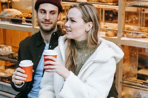 Positive young man and woman spending weekend in cosy bakery having hot drink