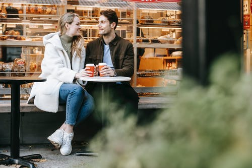 Happy young man and woman having hot tea in cosy cafe