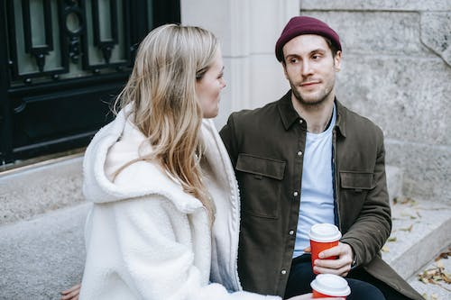 Young couple in casual clothes sitting on stairs outside house and talking while drinking hot coffee in paper cups