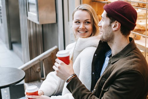 Positive young man and woman drinking coffee in coffee shop