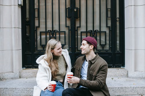 Happy man and woman drinking hot tea and speaking on street
