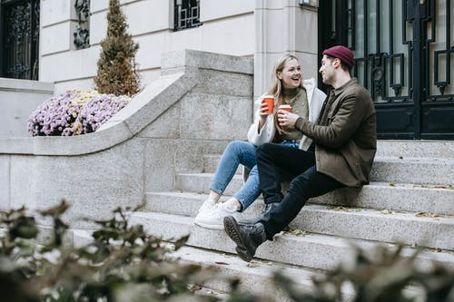 Cheerful friends sitting on steps with paper cups with hot coffee