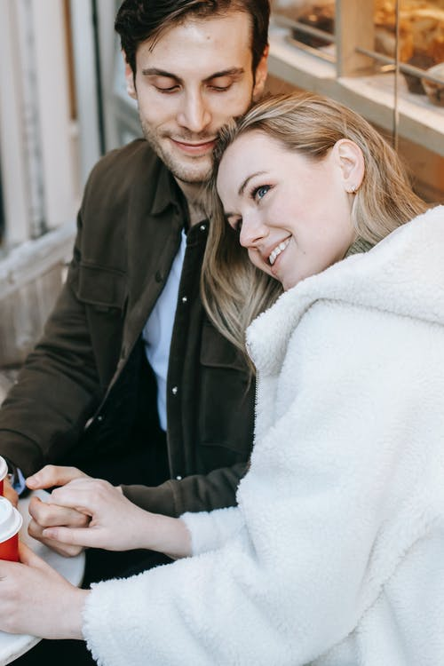 High angle of happy young couple in casual wear spending romantic date in cafe