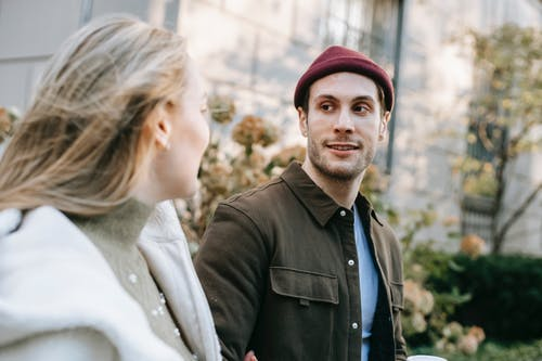 Young smiling man in casual wear and girlfriend walking on street in sunny day looking at each other